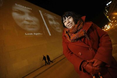 KC Adams stands in front of one of the images from her exhibit which is projected on the Winnipeg Art Gallery.