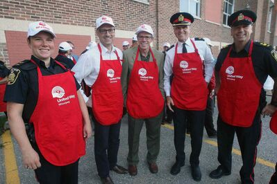 We really are right in the community... even serving up your breakfast. Winnipeg Free Press editor Paul Samyn and publisher Bob Cox (second and third from left) with members of the Winnipeg Police at a United Way community breakfast in September.  (Joe Bryksa / Winnipeg Free Press)