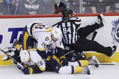 Nashville Predators Matt Hendricks (26), Paul Gaustad (28) and Winnipeg Jets' Anthony Peluso (14) collide with a referee during the first period of Sunday night's game.