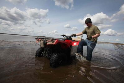 Van Steelandt  uses his quad to get through the high waters on his land.