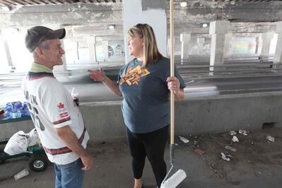 Sel Burrows (left) chats with Point Douglas MLA Bernadette Smith as they join a group painting the dark underpass near Main Street and Higgins Avenue white to brighten it up. (Joe Bryksa / Winnipeg Free Press)