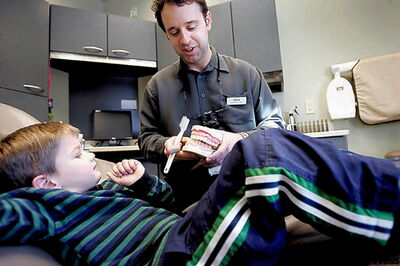 Dr. Zdan Shulakewych shows Benoit Delaquis, 4, how to brush.