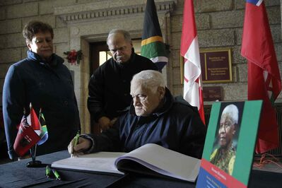 Bill Rhoda signsa book of condolences at the legislature, as son Stan and daughter-in-law Helen watch.