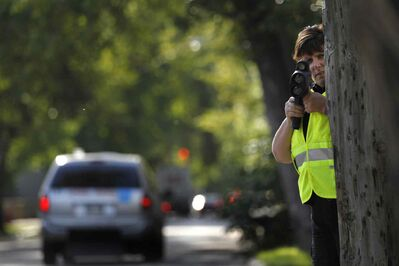 Winnipeg Police Constable Karen McCowan watches for motorists on McDermot Avenue exceeding the 30 km/h speed zone near École Sacré-Coeur School Tuesday morning. Most of the drivers were given warnings to try to educate the motorists of the new school zone speeds that took effect Sept.1.