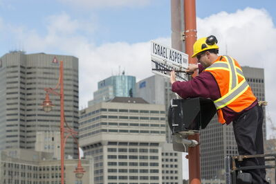]City worker Kris Gustowski changes the street sign of Waterfront Drive to Israel Asper Way.