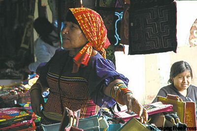 A tattooed Kuna Indian woman sells molas.