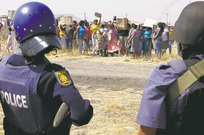 Armed police keep an eye on protesting women at the Lonmin mine on Friday.