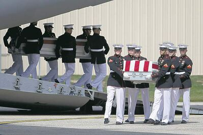 Carry teams move flag draped transfer cases of the remains of the four Americans killed this week in Benghazi, Libya, from a transport plane during the Transfer of Remains Ceremony, Friday, Sept. 14, 2012, at Andrews Air Force Base, Md., marking the return to the United States of the remains of the four Americans killed this week in Benghazi, Libya.