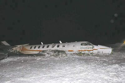 A damaged Perimeter Aviation Fairchild aircraft lies in the snow at Sanikiluaq Nunavut Airport, Saturday, December 22, 2012. The RCMP say a chartered plane with nine people on board crashed on Saturday shortly after 6 p.m. Eight survivors are all being treated for non-life threatening injuries.