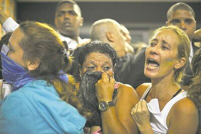 Nicolas Tanner / the associated pressProtestors take cover after police fired tear gas into the street in Rio de Janeiro.