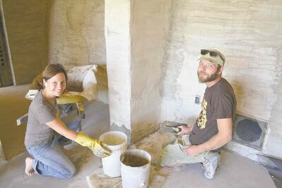 Nicole Bennett and Kris Plantz finish a scratch-coat on the wall of a room in their eco-friendly Earthship home.