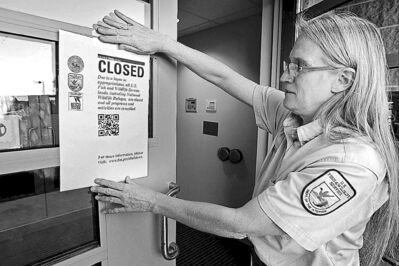 A manager hangs a 'Closed' sign on the Minnesota Valley Wildlife Center in Bloomington on Tuesday.