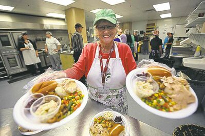 Carole Cockrell serves Thanksgiving meals at Siloam Mission Monday.