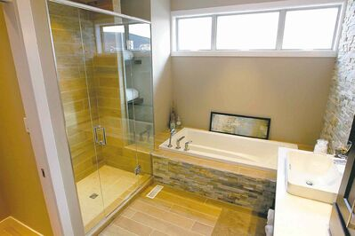 The spacious master ensuite features a six-foot soaker tub set in plank-style ceramic flooring, a six-foot shower and a massive vanity with dual sinks.