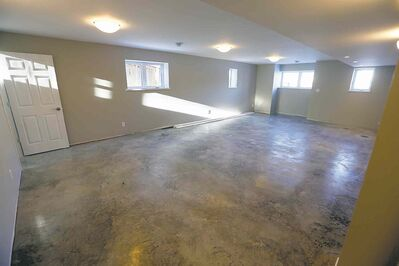 The floor in the spacious basement is polished concrete. The area features two bedrooms and bathroom with a roughed-in kitchen, ideal for a possible apartment setup.