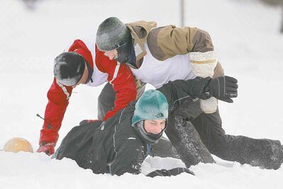 Brett Hudson (from left), Mark Reed and Mitch Decaire of Sue's Socceroos and Mara's Mountaineers play some soccer in the snow at their annual  Snow Bowl at LaVerendrye School. They may have been the only brave souls having some fun outdoors Saturday.