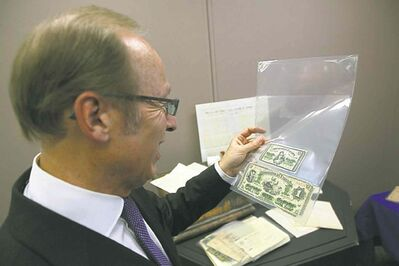 Mayor Sam Katz looks at paper  currency from an old city time  capsule. Items from the capsule will be on display at city hall to mark the 140th anniversary of the first council meeting on  Jan. 19, 1874.