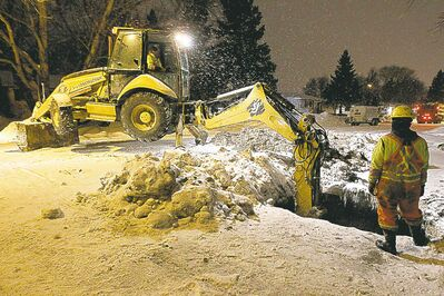 Workers repair another break in the Laxdal Road water main Saturday.