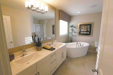 An angled, stand-alone soaker tub is a design focal point in the master bath ensuite.