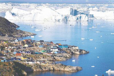 The village of Ilulissat is seen near the icebergs that broke off from the Jakobshavn Glacier last year in Ilulissat, Greenland.