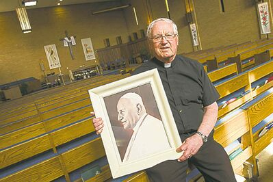 Rev. Art Seaman holds a photo of St. John XXIII.