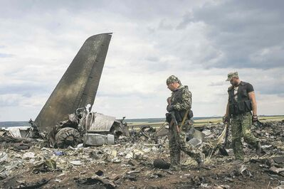 Evgeniy Maloletka / The Associated PressPro-Russian fighters walk past the remnants of a downed Ukrainian army aircraft near Luhansk, Ukraine on Saturday.