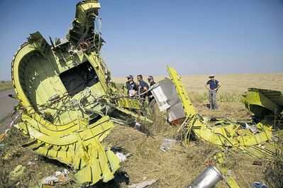 Dmitry Lovetsky / The Associated PressAustralian and Dutch investigators examine pieces of the downed aircraft Friday.