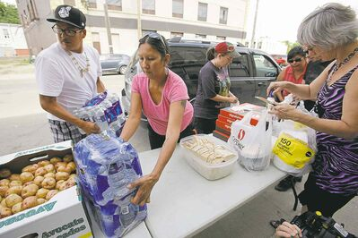 john woods / winnipeg free pressAlthea Guiboche (centre) and volunteers distribute food and clothing Sunday. Guiboche had invited Gord Steeves and his wife, Lorrie (below), to volunteer.