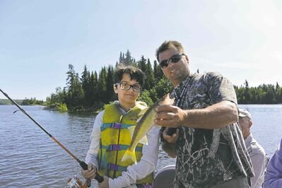 Vance Hrechkosy of Trail End Camp and Outfitters helps Kenna, a student at Lac du Bonnet School, land her first fish Wednesday on the Winnipeg River.
