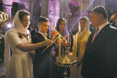 From right, Ukrainian President Petro Poroshenko, his wife Maria, daughter Yevheniya, son Mykhailo and daughter Olexandra light candles during a special service in St. Sophia Cathedral in Kiev, Ukraine, Saturday, Aug. 23, 2014. Ukraine is celebrating the Independence Day on Sunday. (AP Photo/Presidential Press Service, Mikhail Palinchak, Pool)