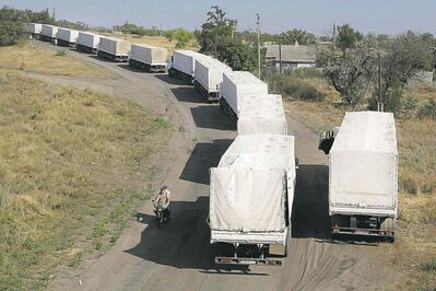Trucks marked as being from a bitterly disputed Russian aid convoy to Ukraine stand in line as they return to Russia on the border post at Izvaryne, eastern Ukraine, Saturday, Aug. 23, 2014. An Associated Press reporter counted 67 trucks entering the border crossing in the Russian city of Donetsk before noon Saturday. Another AP reporter on the Ukrainian side of the border said a line of trucks about 3 kilometers (2 miles) long was waiting to cross. The checkpoint on the Ukrainian side was being operated by separatist rebels, who inspected the trucks. (AP Photo/Sergei Grits)