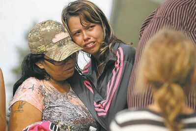 Family members comfort each other as Tina Fontaine�s body is taken away in the hearse after her funeral in Sagkeeng First Nation.