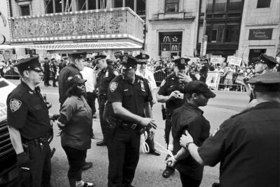 Officers arrest a pair of protesters in front of a McDonald's in New York City's Times Square Thursday.