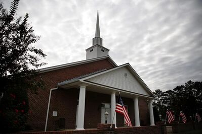 American flags are displayed in front of the First Baptist Church of Gallant, Sunday, Nov. 12, 2017, in Gallant, Ala. Prayer and repentance were among the themes Sunday at the church, which is Alabama Senate candidate Roy Moore's home church. Moore himself wasn't present at First Baptist Church. (AP Photo/Brynn Anderson)