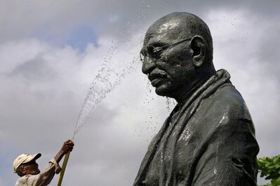 A worker sprays water on a statue of the late Mahatma Gandhi on the eve of his birth anniversary at Gandhi Park in Bhubaneswar, eastern India, Monday, Oct. 1, 2012. The British government plans to erect a similar statue outside of its Parliament buildings.