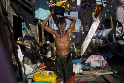A Typhoon Haiyan survivor bathes in the ruins of his home in Guiuan, Philippines. Typhoon Haiyan, one of the most powerful storms on record, hit the country's eastern seaboard Nov. 8, leaving a wide swath of destruction.