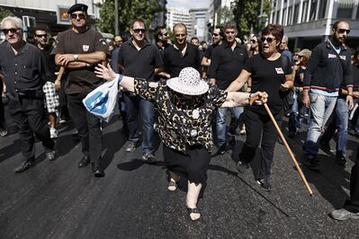 An elderly woman takes part in a protest with municipal police officers central Athens, on Monday , Sept. 23, 2013. About 500 protesters, many wearing black, marched Monday behind a hearse bearing a coffin symbolizing the demise of the municipal police, which is being disbanded as part of plans to trim Greece's bloated public sector.(AP Photo/Petros Giannakouris)