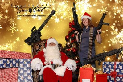 This undated image provided by the Scottsdale Gun Club shows a woman posing with Santa Claus and several guns at the Scottsdale, Ariz. club. Ron Kennedy, general manager of the gun club, says the business got the idea for the photo op last year when a club member happened to come in dressed as Santa and other members wanted their picture taken while they were holding their guns. He says people have used the photos for Christmas cards and Facebook posts. (AP Photo/Scottsdale Gun Club, Gordon Murray)