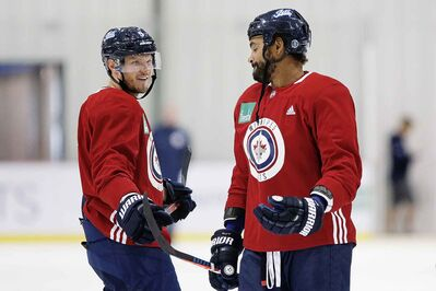 Winnipeg Jets Dmitry Kulikov, left, and Dustin Byfuglien chat during the first day of the Jets NHL training camp, Friday.