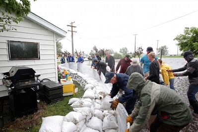 Volunteers help build a sandbag dike around homes in the town of Reston in southwestern Manitoba on Sunday after incessant rainfall creating overland flooding in the community. Reston was hit hard by flooding just over a year ago.