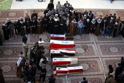 FILE - In this file photo taken Tuesday, Jan. 21, 2014, mourners pray over five coffins draped with Iraqi flags for Iraqi soldiers killed by al-Qaida militants in Anbar province during their funeral procession inside the shrine of Imam Ali in Najaf, 100 miles (160 kilometers) south of Baghdad, Iraq. The Islamic State of Iraq and the Levant has claimed responsibility for the execution-style killings of the four Iraqi commandos near Fallujah, Anbar province. The other soldier was killed during clashes. (AP Photo/Jaber al-Helo, File)