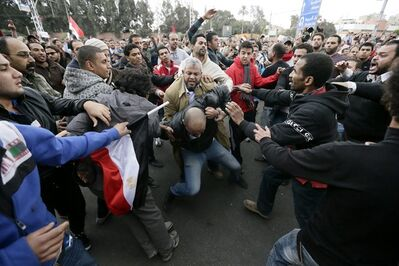 FILE - In this Wednesday, Dec. 5, 2012 file photo. supporters of then- Egyptian President Mohammed Morsi's beat an opponent, center, during clashes outside the presidential palace, in Cairo, Egypt. Egyptian authorities switched the venue for the trial of the former Islamist president on Sunday, Nov. 3, 2013 a last-minute change made after the Muslim Brotherhood called for mass demonstrations at the original location. The trial of Morsi, now to be held east of the capital on Monday, could lead to another round of bloodshed as his supporters look likely to face an emboldened security apparatus that has boosted its forces for the hearing. (AP Photo/Hassan Ammar, File)