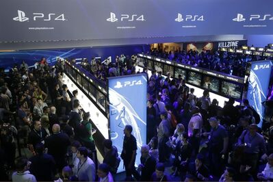 "FILE - In this June 11, 2013 file photo, show attendees play video games on the new Sony PlayStation 4 at the Sony booth during the Electronic Entertainment Expo, in Los Angeles. Twitch is coming to the PlayStation 4; the popular streaming video service that allows gamers to broadcast footage online was previously announced as a feature for Microsoft's Xbox One. Sony said Tuesday, Aug. 20, 2013, the service would also be available on the PS4, which adds a ""Share"" button to its new controller. (AP Photo/Jae C. Hong, File)"