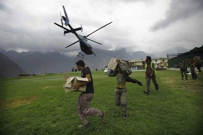 Indian civilians get ready to load relief material for flood affected victims on a helicopter at a makeshift helipad at Joshimath, in northern Indian state of Uttarakhand, Monday, June 24, 2013. A top official said the death toll in northern India could rise as army soldiers clear the debris from towns and villages flattened by landslides and monsoon flooding.Home Minister Sushilkumar Shinde said the number of people who have perished in the floods that washed away thousands of homes could go beyond the 1,000 deaths reported so far (AP Photo/Rafiq Maqbool)