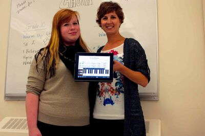 River East Collegiate choral director Nicole Ens shows off her composition of the Gershwin tune I've Got Rhythm on her iPad alongside Grade 12 student Maria Andersson.