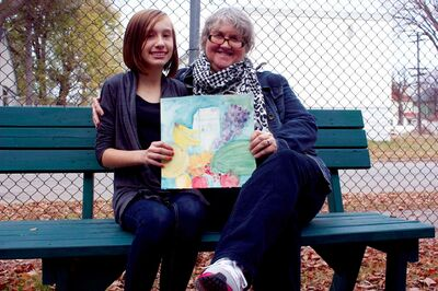 Grade 8 artist Caitlyn Hudson holds up her piece used for the Local Colour Art Group's fall show invitation alongside mentor Thora Barnett.