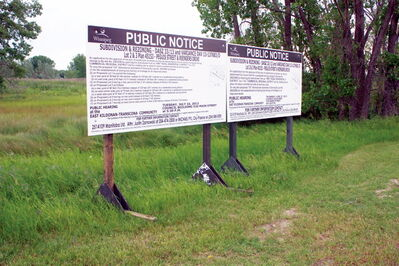 Signs for the public hearing regarding the Shops of Kildonan Mile development on July 16, 2013 are shown.