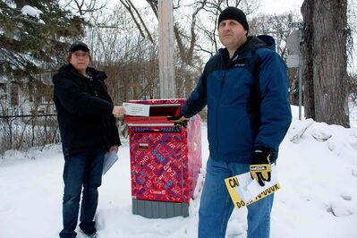 Canada Post employees Tim Kerr and Glenn Bennett are shown near a Canada Post mailbox near Kerr's East Kildonan home. The pair are concerned about proposed changes.