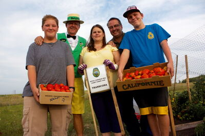 From left to right: Evan Evaniuk, Hi Neighbour Sam (Peter Martin), Lt. Shari Howells, Lt. Mike Gnutel, and Riley Howells are shown with the tomatoes the RCSCC #350 Transcona Sea Cadets grew for Winnipeg Harvest.