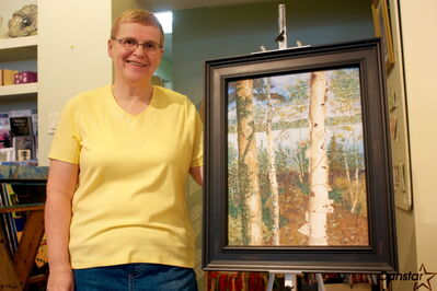 Glenelm artist Elizabeth Delgatty displays a painting to be featured in her Trees, Trees, Trees! Paintings of Peaceful Places exhibit at Wayne Arthur Gallery.